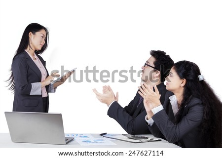 Portrait of two businesspeople giving applause to their leader after business presentation - stock photo