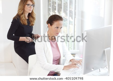 Portrait of two businesswoman working together on new project while sitting at office in front of computer. - stock photo