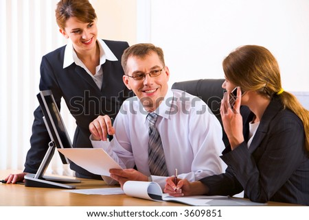 Portrait of two businesswomen and businessman discussing questions sitting at the table with a monitor and opened documents on it