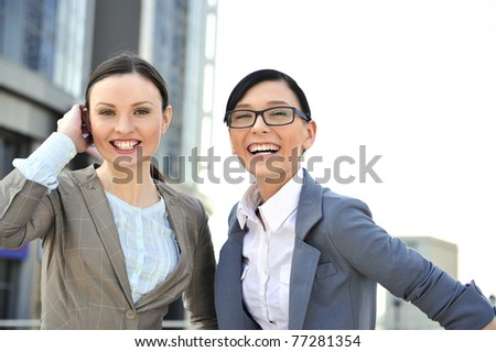Portrait of two businesswomen outside.  Outside background. - stock photo