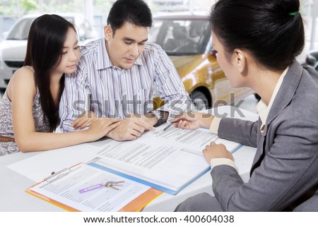 Portrait of two car buyers reading a document of the rule to buy a car credit in the showroom