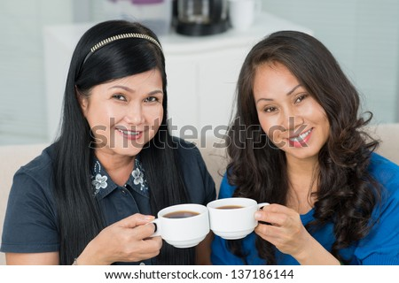 Portrait of two charming ladies in their fifties drinking tea - stock photo