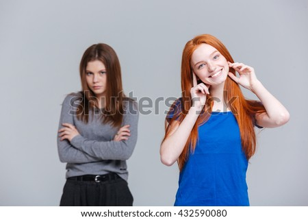 Portrait of two cheerful and unhappy young women over white background - stock photo