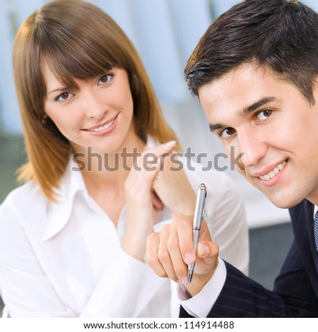 Portrait of two cheerful businesspeople at office - stock photo