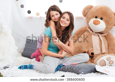 Portrait of two cheerful charming sisters sitting in children room at home  - stock photo