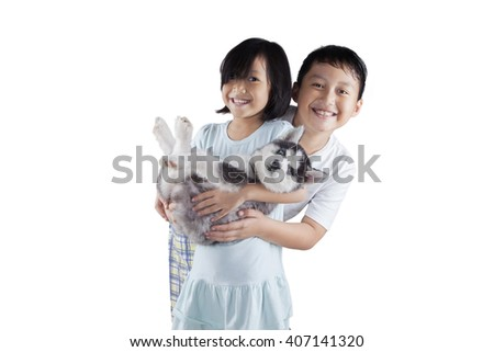 Portrait of two cheerful children playing in the studio while holding a cute siberian husky puppy - stock photo