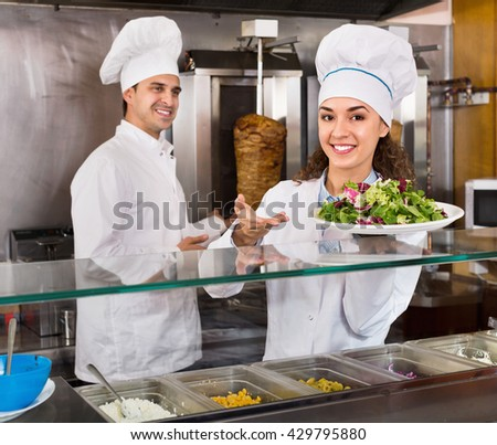 Portrait of two cheerful friendly hospitable chefs with kebab at fast food place - stock photo