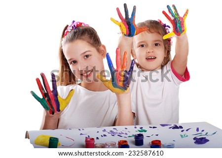 Portrait of two cheerful girls show their hands painted in bright colors - stock photo