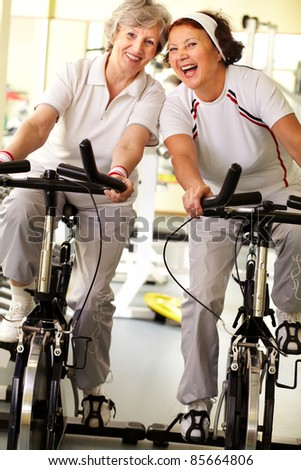 Portrait of two cheerful grandmas exercising on simulators - stock photo