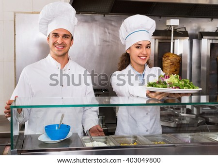 Portrait of two cheerful smiling  hospitable chefs with kebab at fastfood place - stock photo