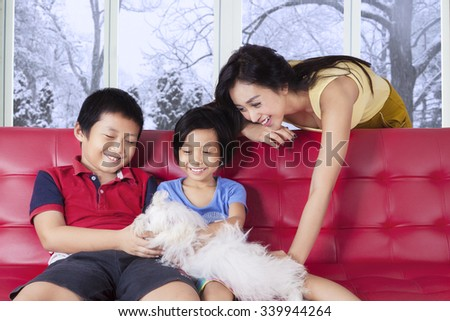 Portrait of two children and their mother playing puppy on the sofa, shot at home - stock photo