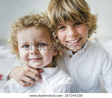 Portrait of two children blond brothers playing in their bedroom - stock photo