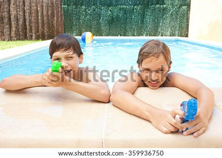 Portrait of two children friends smiling on the edge of a swimming pool together playing with water guns on a sunny summer holiday in home garden, outdoors. Action games and kids fun, house exterior. - stock photo