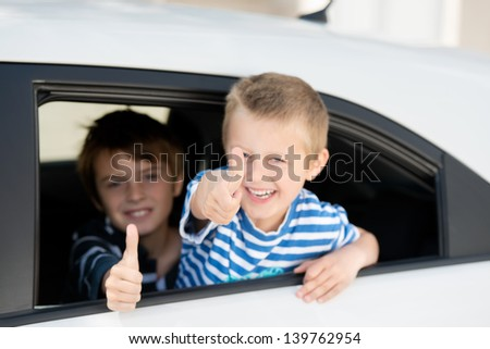 Portrait of two children inside the car showing thumbs up sign