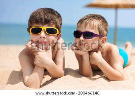 Portrait of two children on the beach - stock photo