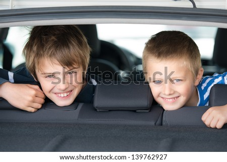 Portrait of two children smiling inside the car