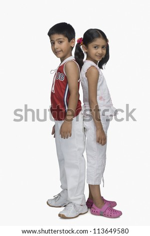 Portrait of two children standing back to back - stock photo