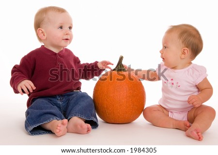 Portrait of two children with a pumpkin. Baby girl is looking at the pumpkin stalk. Baby boy is looking up and right, a perfect place to put ad copy or design elements. - stock photo