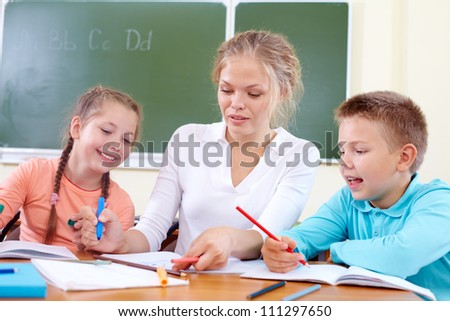 Portrait of two classmates and their teacher drawing with highlighters at lesson - stock photo