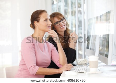Portrait of two confident creative women working on computer at office. - stock photo