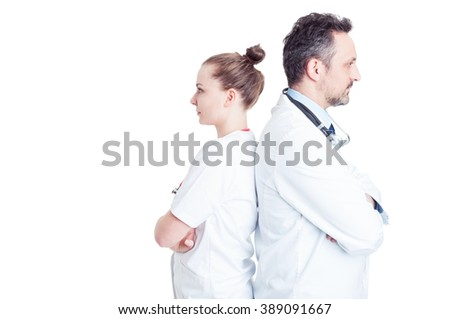 Portrait of two confident doctors standing back to back with crossed hands isolated on white background