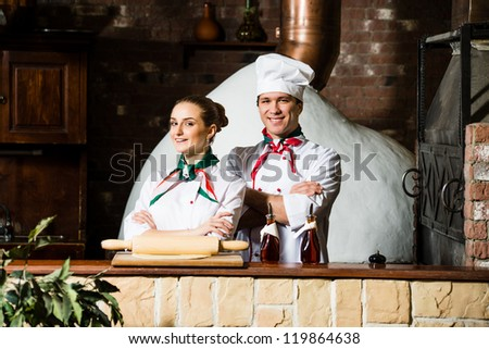 portrait of two cooks, crossing his arms and looking at the camera - stock photo