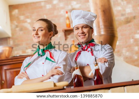 Portrait of two cooks with crossed arms looking at the camera - stock photo