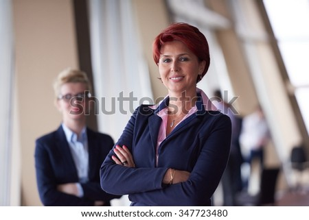 portrait  of two corporate business woman at modern bright office interior standing in group as team - stock photo