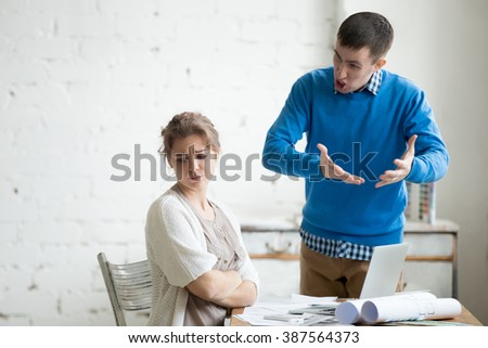 Portrait of two coworkers arguing at work. Staff in the middle of argument at modern office. Young furious man yelling at annoyed stressed woman with crossed arms. Negative human emotions
