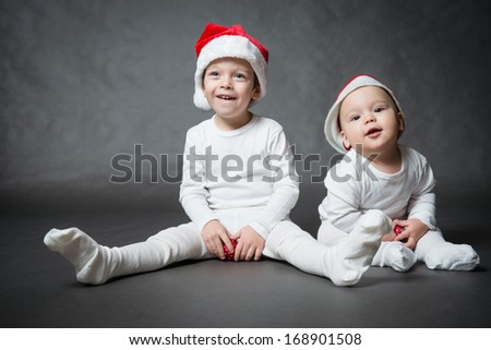 Portrait of two cute boys in Santa hats, gray background - stock photo