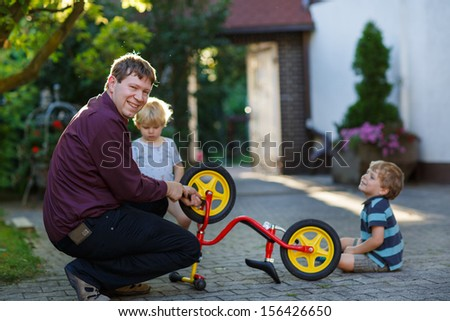 Portrait of two cute boys repairing bicycle wheel with father outdoors - stock photo