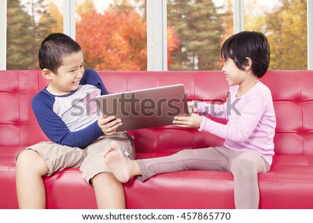 Portrait of two cute children fighting on the sofa to take laptop computer, shot at home with autumn background on the window