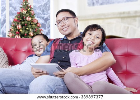 Portrait of two cute children sitting on the sofa with their father and smiling at the camera while holding tablet
