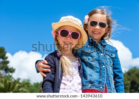 Portrait of two cute kids wearing sunglasses outdoors. - stock photo