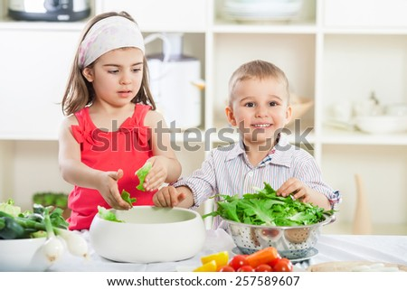 Portrait of two cute little children preparing salad