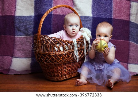 Portrait of two cute little girls. One girl sitting in a basket, the second girl sitting beside her and gnawed apple