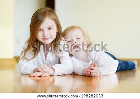 Portrait of two cute sisters at home