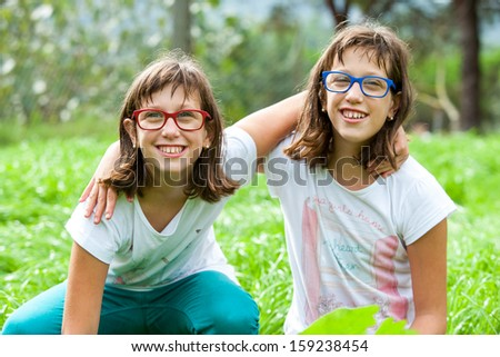 Portrait of two disabled twin sisters embracing outdoors.