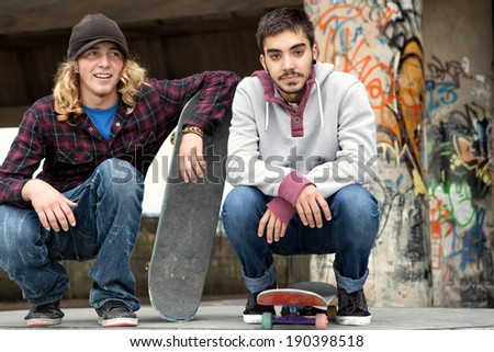 Portrait of two diverse teenagers relaxing together on a skateboarding park, smiling and enjoying a day out with their skate boards being active, outdoors. Teenagers on vacation having fun, lifestyle. - stock photo