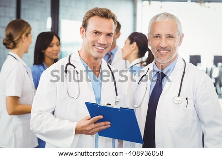 Portrait of two doctors with clipboard in hospital and colleagues standing behind and discussing - stock photo