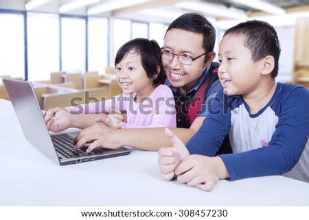 Portrait of two elementary school student using laptop computer with their teacher in the classroom