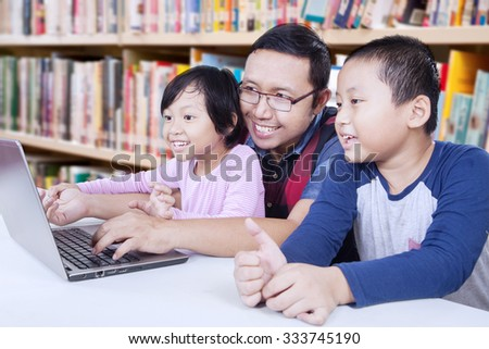 Portrait of two elementary school student using laptop for studying with their teacher in the library - stock photo