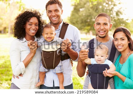 Portrait Of Two Families With Baby Carriers In Park - stock photo