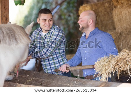 Portrait of two farmers with a pitchforks in settlement  - stock photo