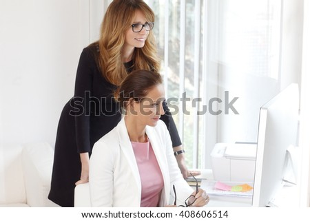 Portrait of two female colleagues discussing work on a computer after business meeting.  - stock photo