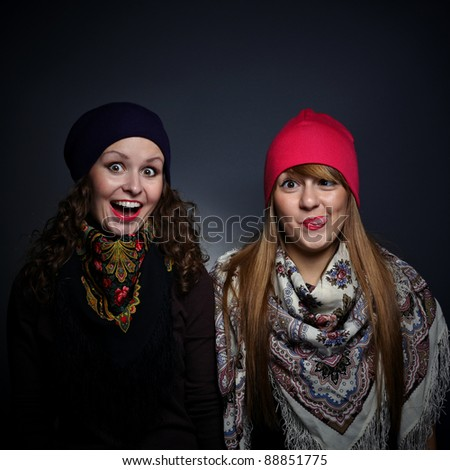 Portrait of two female friends in playful mood against grey background - stock photo