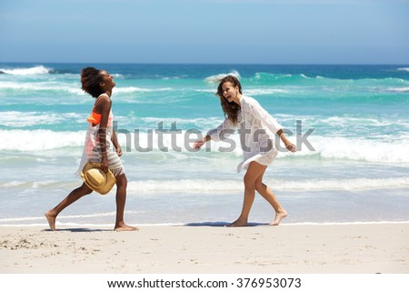 Portrait of two female friends walking and smiling at the beach
