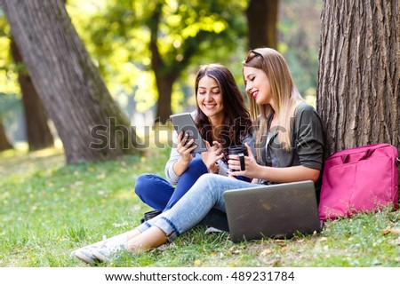 Portrait of two female student sitting in park with laptop and blueprints, education and learning concept.