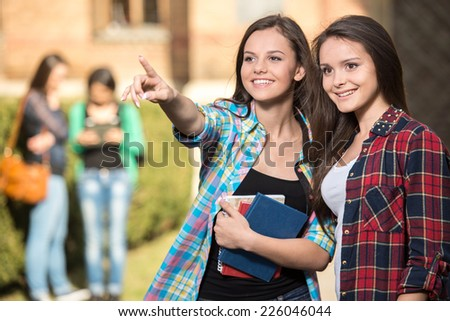 Portrait of two female students at the college, outdoors. The students in the background. - stock photo