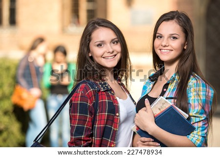 Portrait of two female students at the college, outdoors. The students in the background.